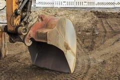 在沙子的挖掘机铁锹 库存照片