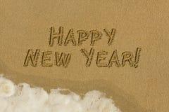 在沙子的新年快乐消息 免版税图库摄影
