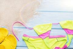 在沙子的明亮的比基尼泳装,黄色页岩 免版税库存图片