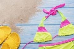 在沙子的明亮的比基尼泳装,黄色页岩 库存照片