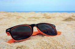 在沙子的橙色太阳镜与背景的海 免版税库存图片