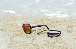 在沙子的残破的太阳镜 免版税库存图片