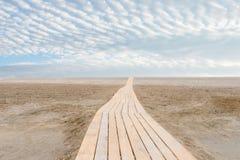 在沙子的海滩中央木道路 免版税库存图片