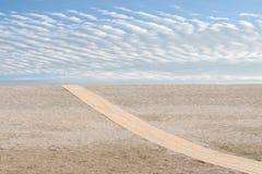 在沙子的海滩对角木道路 免版税库存图片