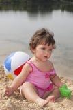 在沙子的海滩小女孩坐并且使用与buc 库存图片