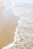 在沙子的海洋海浪 免版税库存图片