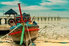 在沙子的渔船在桥梁和海附近靠岸 在天堂热带海滩和手段概念的放松 在海滩的垃圾 免版税库存照片