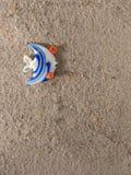 在沙子的玩具鱼 免版税库存照片