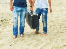 在沙子的男性和女性脚在带着一个皮革手提箱的海附近 免版税库存图片