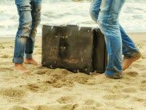 在沙子的男性和女性脚在带着一个皮革手提箱的海附近 免版税图库摄影