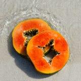 在沙子的番木瓜切片在水 库存图片