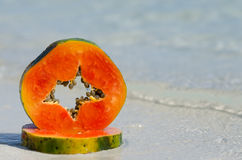 在沙子的番木瓜切片在水 免版税库存照片