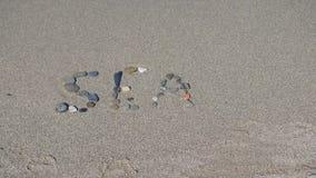 在沙子的登记 海的词 免版税库存照片