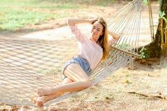 在沙子的白色柳条吊床的年轻白肤金发的女孩,佩带的牛仔裤短缺 库存图片
