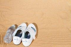 在沙子的白色运动鞋 库存图片