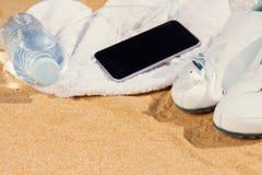 在沙子的白色运动鞋 免版税图库摄影