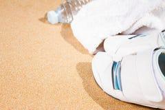 在沙子的白色运动鞋 免版税库存图片