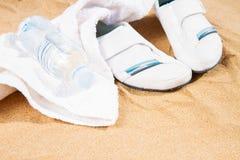 在沙子的白色运动鞋 免版税库存照片