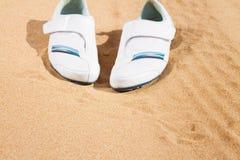 在沙子的白色运动鞋 库存照片