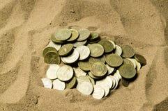 在沙子的硬币 免版税图库摄影