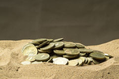 在沙子的硬币 免版税库存图片