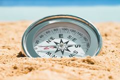 在沙子的磁性银色指南针 免版税库存图片