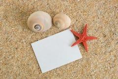 在沙子的笔记与壳 免版税库存图片