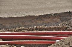 在沙子的管子在路附近 库存图片