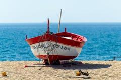 在沙子的红色划艇在海附近 免版税库存照片
