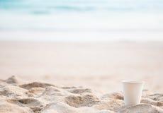 在沙子的纸杯在海滩 免版税库存照片