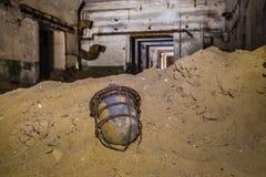 在沙子的老打破的生锈的苏联灯笼在被放弃的地堡背景  免版税库存图片