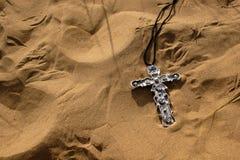 在沙子的耶稣受难象 库存图片