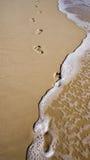在沙子的脚印与波浪 库存图片