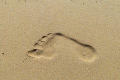 在沙子的脚印刷品 免版税库存照片