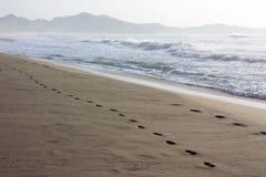 在沙子的脚印在海滩肋前缘Rei在撒丁岛 库存照片