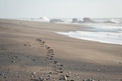 在沙子的脚印在海滩 免版税库存图片