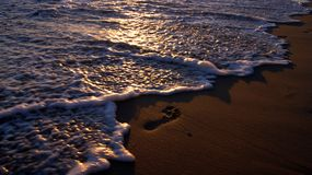 在沙子的脚印由海洋 免版税库存照片