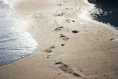 在沙子的脚印由海 在含沙岸的海波浪在轨道旁边 美好的晴朗的bokeh 免版税库存照片