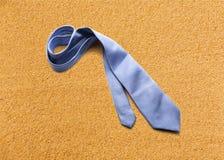 在沙子的蓝色领带 免版税库存照片