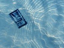 在沙子的袖珍相机在海水下 免版税库存照片