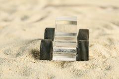 在沙子的透明异丁烯酸玩具汽车 免版税库存照片