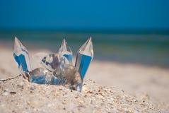 在沙子的透明玻璃水晶在蓝色海和蓝天背景  免版税库存图片