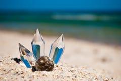 在沙子的透明玻璃水晶在蓝色海和蓝天背景  免版税库存照片