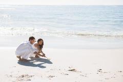 在沙子的逗人喜爱的夫妇图画 库存照片