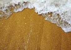 在沙子的通知和泡沫 库存照片
