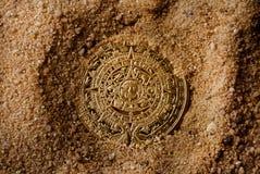 在沙子的阿兹台克硬币 免版税图库摄影