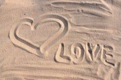 在沙子的题字爱与心脏在海边 免版税库存照片