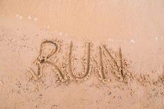 在沙子的题字:奔跑 免版税图库摄影
