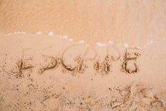 在沙子的题字:逃命 库存照片