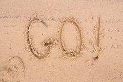 在沙子的题字:去! 免版税库存图片